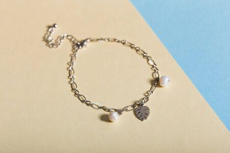 Women's Jewelry. Trendy jewelry on coloured background. Flat lay.