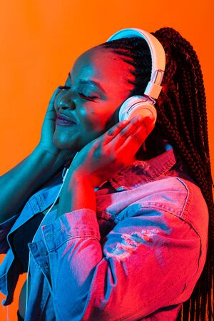 African american young woman listening to music online dancing and singing with headphones, neon light. Music and technology concept.