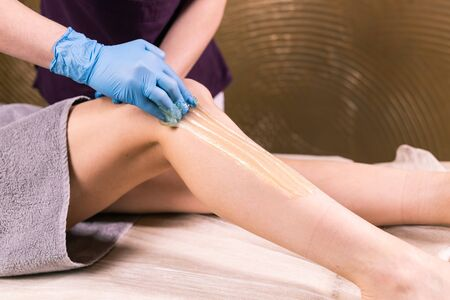 Sugaring epilation skin care with liquid sugar at legs. You can see her smooth and hair free legs after hair removal close-up. Beauty and cosmetology.