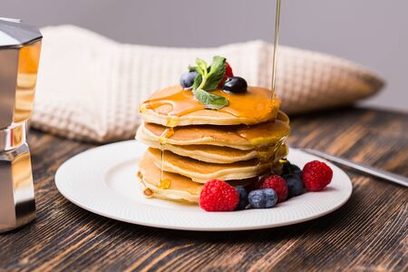 Woman pouring maple syrup on tasty pancakes Standard-Bild