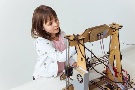 Cute girl with 3d printed shutter shades is watching her 3d printer as it prints her 3d model.