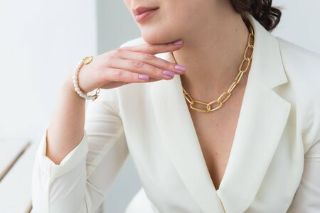 Close-up of beautiful woman wearing necklace and the pearl bracelet. Accessories, jewelry and bijouterie.