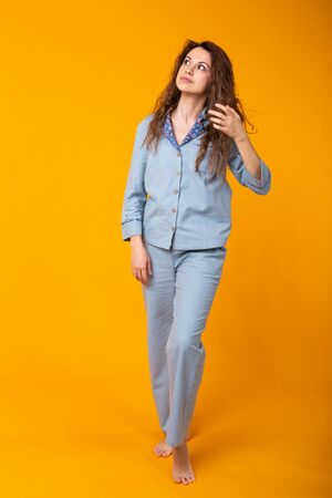 Close up young woman in blue home wear. Isolated on yellow background. Pajama concept.