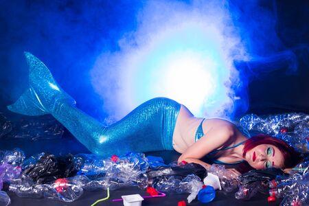 Sad fairytale mermaid in polluted ocean. Plastic trash and garbage in water. Environmental problem, plastic bag and bottles polluting a coral reef Standard-Bild