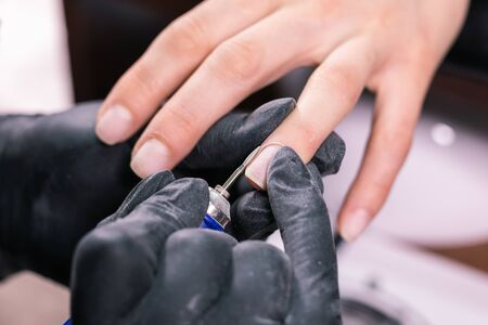 Close-up professional beautician hands working with electric drill on client fingernails. Procedure applying artificial fingernails. Hands of manicurist with tool. Manicurist in gloves removes cuticle