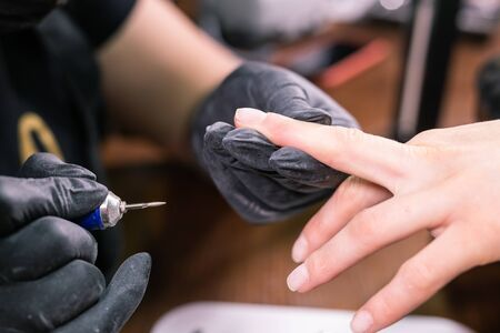 Closeup shot of hardware manicure in a beauty salon. Manicurist is applying electric nail file drill to manicure on female fingers.