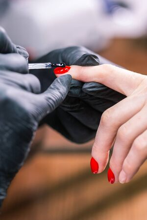 Close Up of master in rubber gloves covering red nails with top coat in the beauty salon. Perfect nails manicure process. Gel polish concept