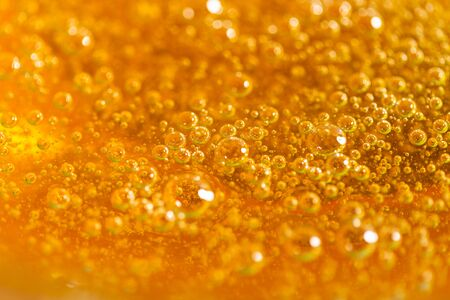 Detail of abstract orange bubble, can be used for background. Paste for sugaring close-up. Depilation and hair removal concept. Macro.