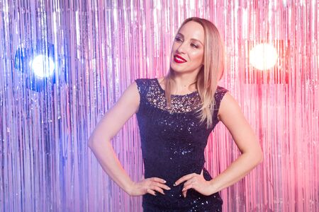 Beautiful blonde woman in the disco club. Party, holidays and celebration concept.