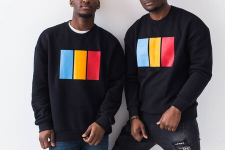 Street fashion and friendship concept - Two happy african american young men in black stylish sweatshirts, close-up.