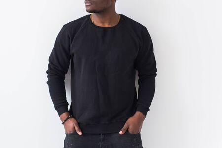 Gros plan sur un homme afro-américain posant en sweat noir sur fond blanc. Photo de mode de rue pour les jeunes avec une coiffure afro.