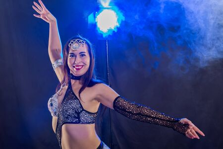 Young woman dancing in Tribal Fusion style. Belly dance on the stage.