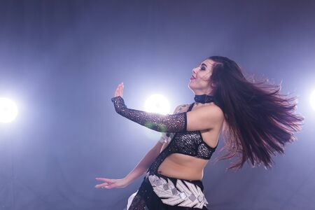 Portrait of a woman in oriental costume performing belly dance. Tribal fusion dance concept. 免版税图像