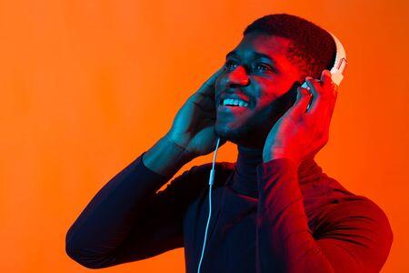 Neon portrait of handsome african american man in headphones. Listening to music. Archivio Fotografico
