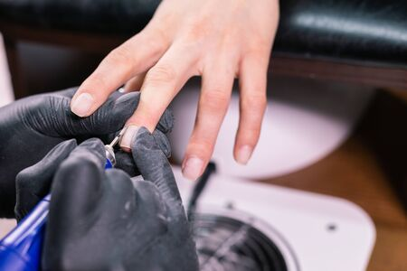 Hardware manicure in a beauty salon. Female manicurist is applying electric nail file drill to manicure on female fingers. Mechanical manicure close-up. Body care. 版權商用圖片 - 146700610