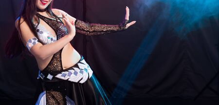 Belly dancer. Young attractive woman dancing tribal fusion on the stage. Oriental exotic dance. 免版税图像