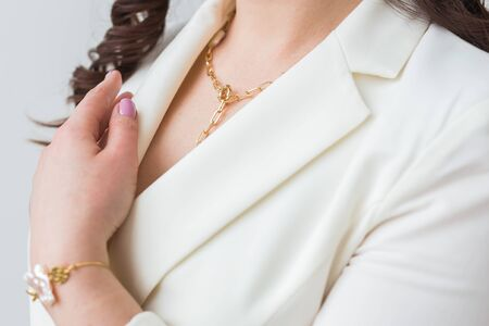 Close-up of woman wearing a gold necklace. Jewelry, bijouterie and accessories concept. Imagens