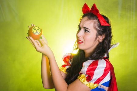 Woman holding hazardous radioactive apple. Nuclear and radiation measurement concept.