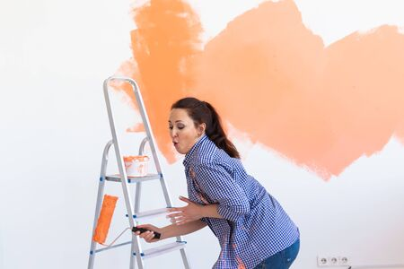 Dancing funny woman painting the walls of new home. Renovation, repair and redecoration concept.
