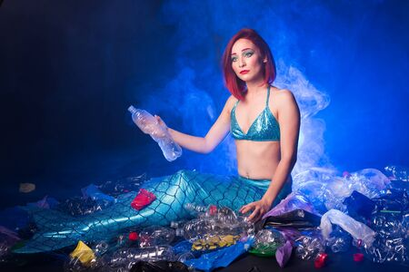 Sad fairytale mermaid in polluted ocean. Plastic trash and garbage in water. Environmental problem, plastic bag and bottles polluting a coral reef. Фото со стока