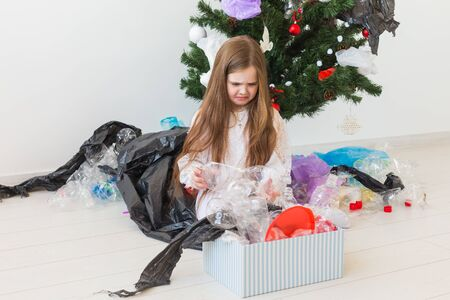 Shocked little child girl looks with opened eyes and worried expression, holding box with various plastic wastes over christmas tree background.