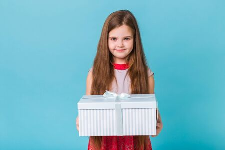 holidays, presents, christmas, childhood and birthday concept - smiling little girl with gift box over blue background