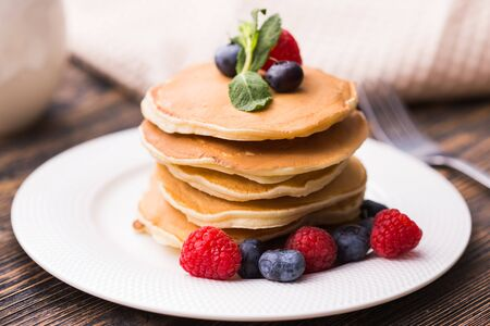 Homemade american pancakes with fresh blueberry and raspberries. Healthy morning breakfast. Rustic style. Фото со стока