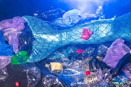 Close-up of fantasy mermaid in deep ocean sad because water pollution. Plastic trash and bottles pollution in ocean. Ecocatastrophe, garbage and plastic recycling concept.