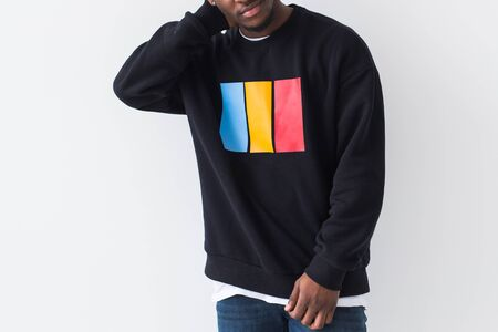 Street fashion concept - Studio shot of young handsome African man wearing sweatshirt against white background, close-up. Фото со стока