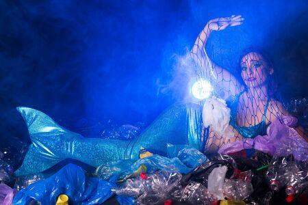 Fantasy mermaid in deep ocean shocked because water pollution. Plastic water bottles and bags pollution on sea floor. Environmental problem.