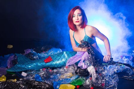 Sea plastic pollution concept. Mermaid in the ocean. Plastic is everywhere. Environmental protection. Фото со стока