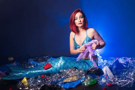 Sad fairytale mermaid in polluted ocean. Plastic trash and garbage in water. Environmental problem, plastic bag and bottles polluting a coral reef. Stock Photo
