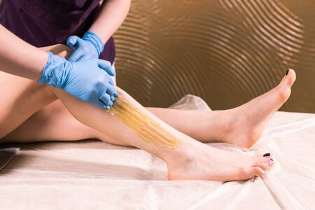 Sugaring epilation skin care with liquid sugar at legs. You can see her smooth and hair free legs after hair removal close-up. Beauty and cosmetology concept.