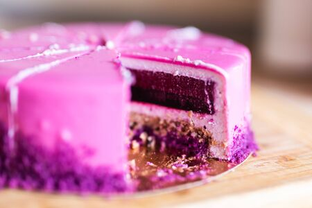 Pink and violet birthday cake without one piece. Dessert, holidays and delicious concept. 免版税图像
