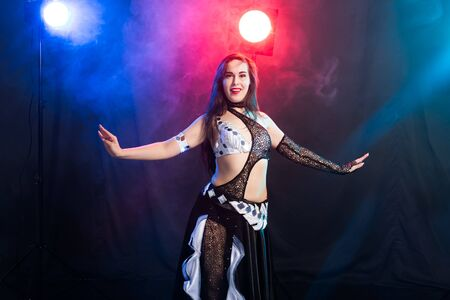 Belly dancer. Young attractive woman dancing tribal fusion on the stage. Oriental exotic dance. Imagens