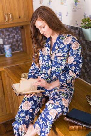 Young red-haired woman relaxing at home with books. Quarantine, isolation, coronavirus pandemic world. Stay at home. Stock Photo