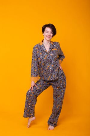 Cheerful woman in home wear pajama studio lifestyle yellow background emotions. Foto de archivo