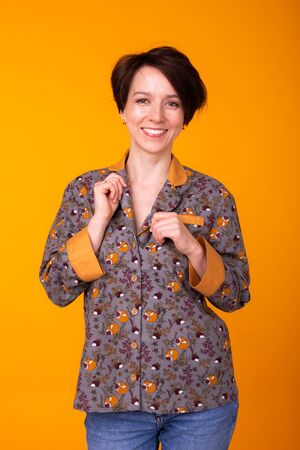 Fashion portrait pretty cool girl in home wear pajama having fun over colorful yellow background. 写真素材