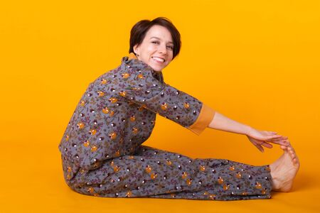 Excited young woman with black hair in home wear pajama, widely smiling having fun. Isolated on yellow background. Copy spase.