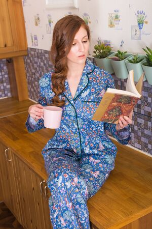 Young red-haired woman relaxing at home with books. Quarantine, isolation, coronavirus pandemic world. Stay at home.