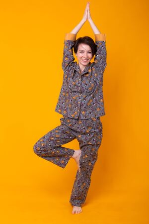 Excited young woman with black hair in home wear pajama, widely smiling having fun. Isolated on yellow background. Yoga concept.
