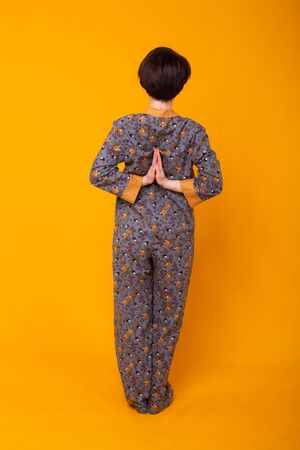 Fashion portrait pretty cool girl in homewear pajama having fun over colorful yellow background 写真素材