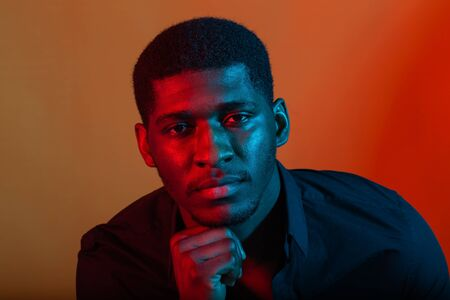Dark neon portrait of young man wearing in shirt. Red and blue light. Technology