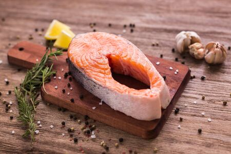 Fresh salmon fillet on a board, food close up. Diet, omega vitamins and seafood concept.