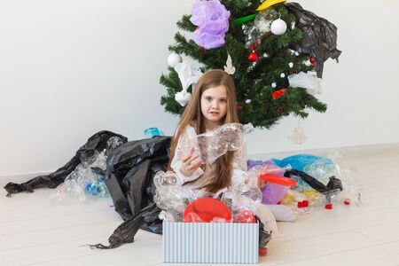 Shocked little child girl looks with opened eyes and worried expression, holding box with various plastic wastes over christmas tree background. Reklamní fotografie