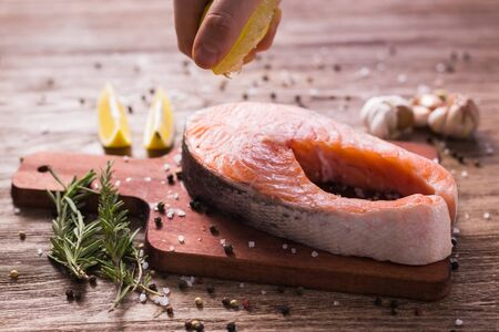 Japanese or Oriental cuisine, Seafood, Chef pouring lemon juice freezes in motion on the steak of fish with ingredients on the table. Healthy and healthy food, sale of seafood and fish shops concept