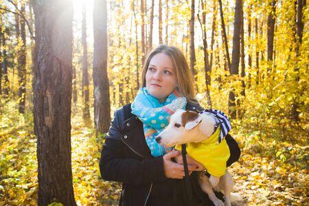 Femme avec un chien jack russell terrier. Concept d'amitié et d'animal de compagnie. Petit chien marchant dans le parc en automne.