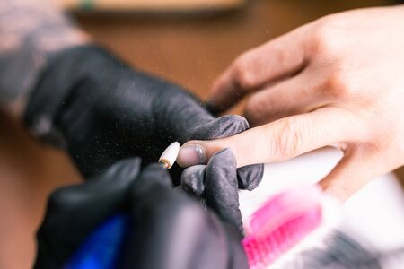 Close-up of hardware milling cutter for removing gel polish. Apparatus manicure in beauty salon. Manicurist with electric nail drill remove old gel from client nails. Process of replacing shellac.