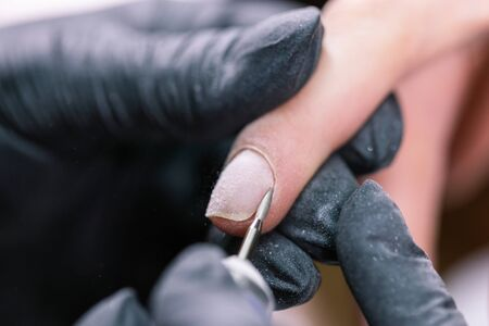 Close-up shot of hardware manicure in a beauty salon. Manicurist is applying electric nail file drill to manicure on female fingers.