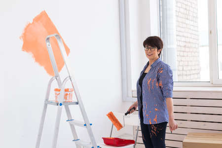 Happy middle-aged woman painting interior wall with paint roller in new house. A woman with roller applying paint on a wall.